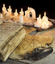Candles burn behind esoteric witchcraft books