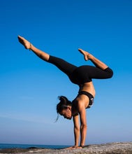 Woman practicing advanced yoga pose on rock near ocean