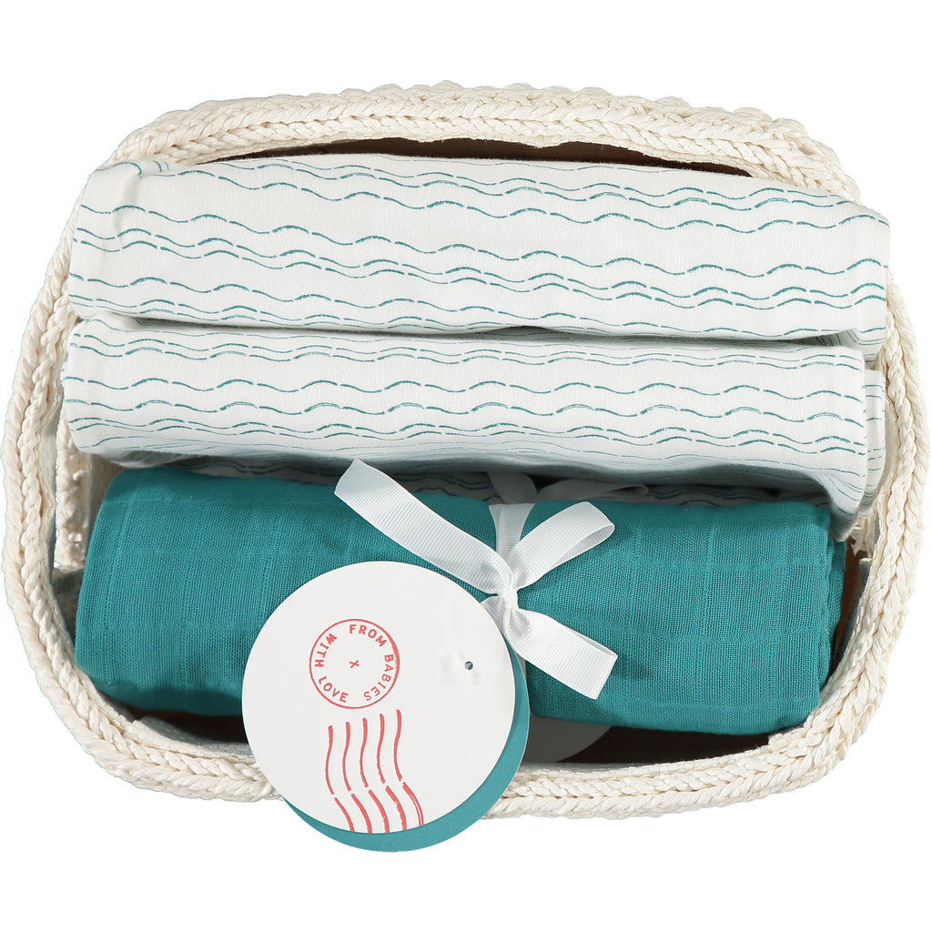 Swaddles in basket - Send love and kindness with our Waves of Joy and teal organic muslin baby shawl + swaddling wraps, a heartfelt and beautiful baby gift.