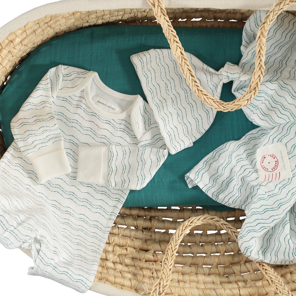 Baby basket - Send love and kindness with our Waves of Joy organic baby grow, knot hat, bandana bib and two muslin baby shawl + swaddling wraps, a heartfelt and beautiful baby gift.