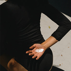 a white woman with brunette long hair leans over with her arm up to shade her face. She is wearing a white playsuit.
