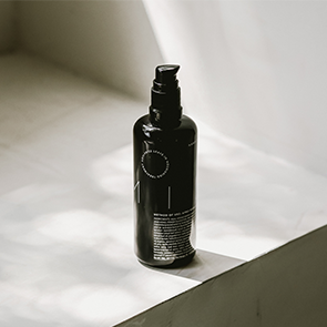 a black glass bottle sits on a beige windowsill and is lit with subtle sunlight. The bottle has white text that wraps around the bottle listing Milk's ingredients and Method of Use.