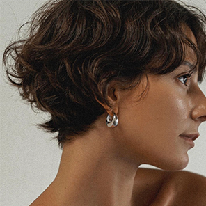 A tanned woman with short, wavy, brunette hair is seen in close up profile wearing a silver hoop earring.