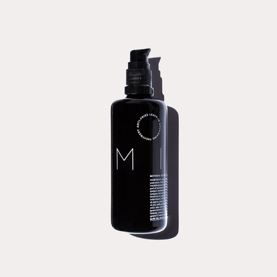 milk in its black glass bottle lays against a beige background