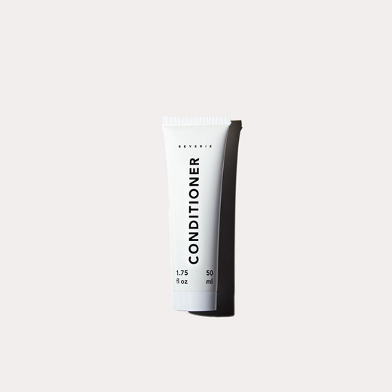 A small white tube with black text reads: Conditioner. It sits against a beige background.