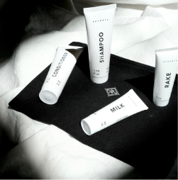 All the white travel tubes of Milk, Conditioner, Rake, and Shampoo are laying on a black box with the Reverie logo on it in white. The box sits on a bed with a white comforter on it. Mini Milk and Mini Conditioner are laying on their sides, while Shampoo and Rake are upright.