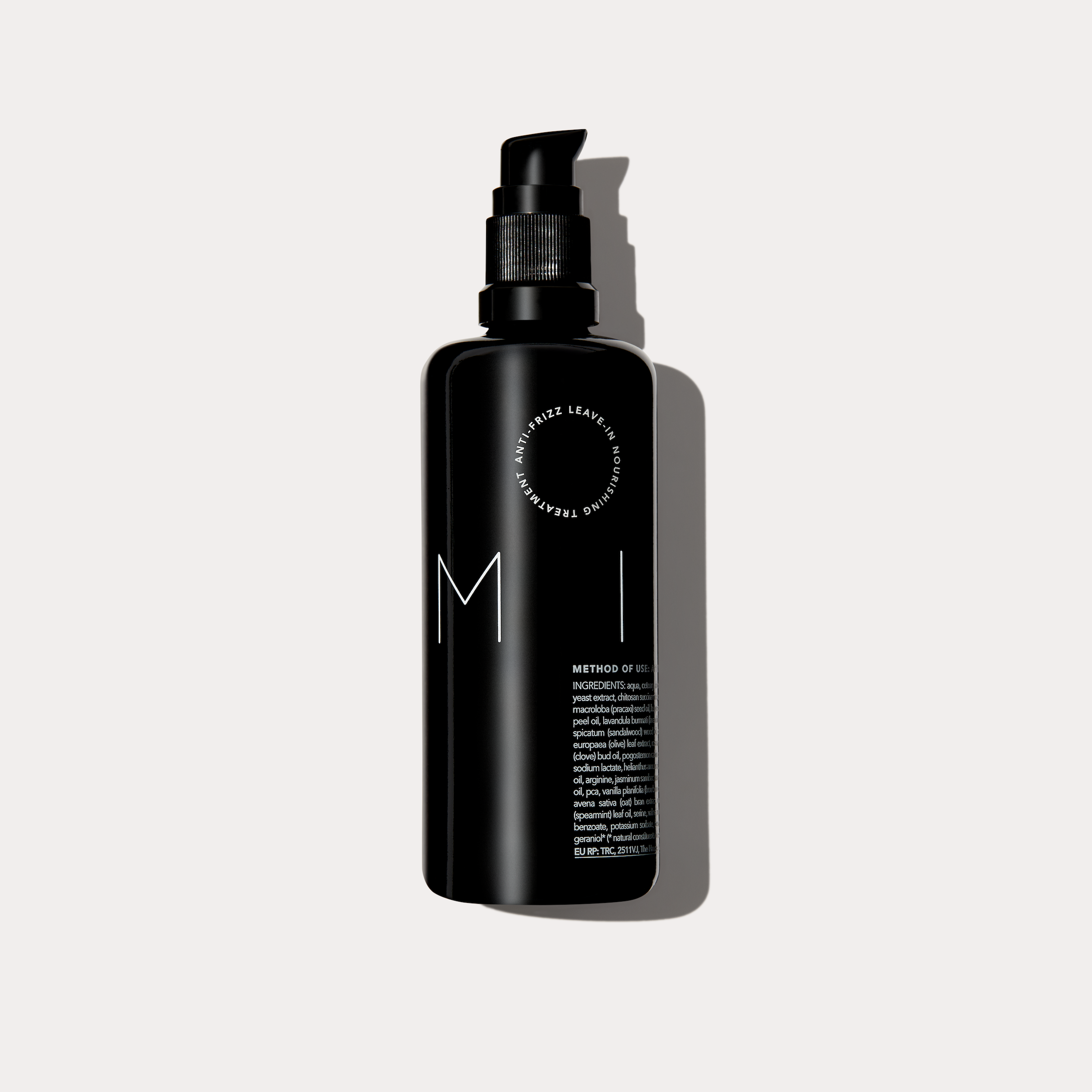 Milk Anti Frizz Leave in treatment black glass bottle against an off white background