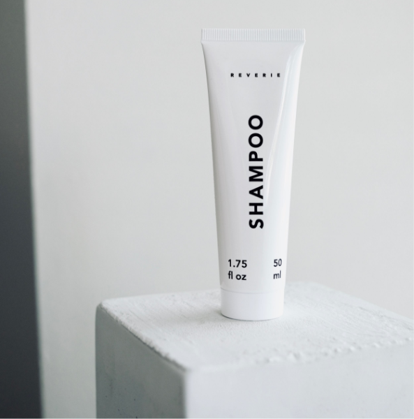 A small white tube with black text reads: Shampoo. The tube sits on a white shelf.