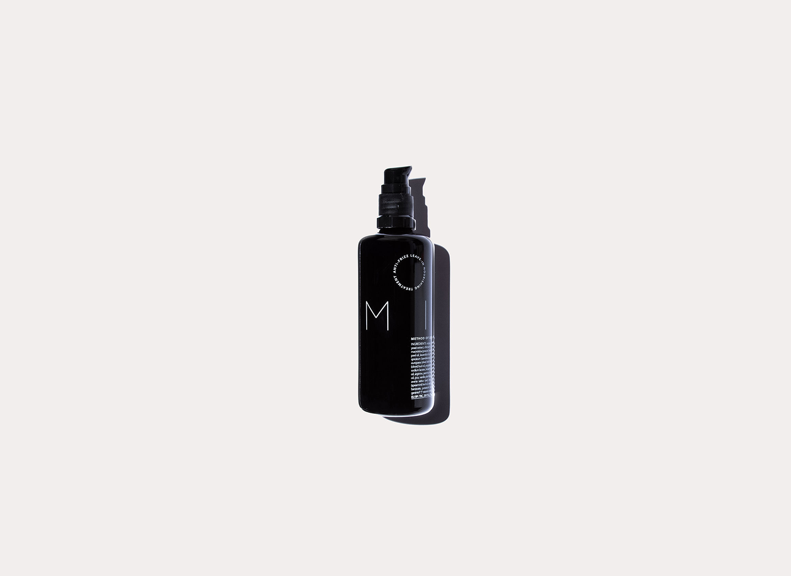 Milk Anti-Frizz Leave-in Treatment black bottle lays against an off white background