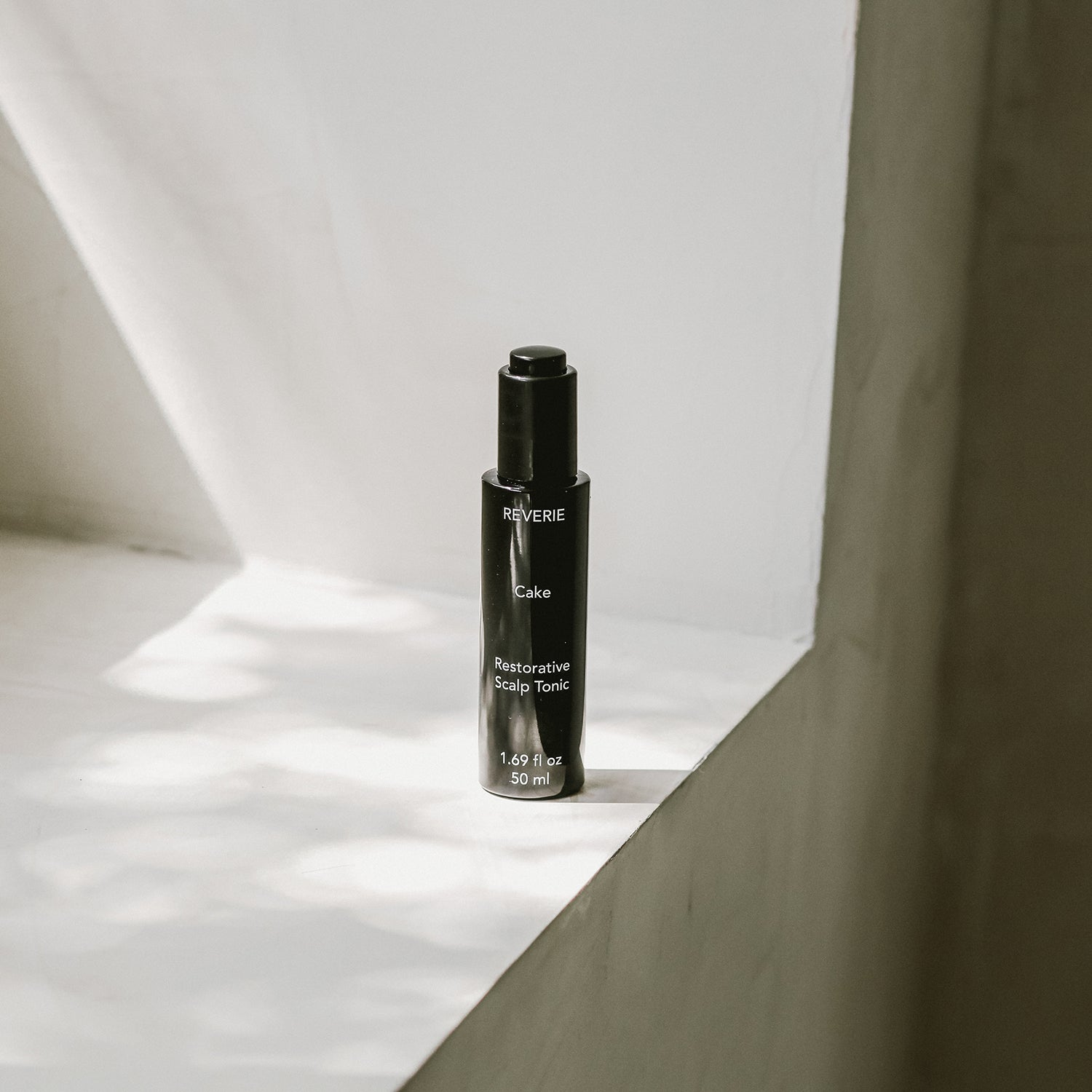 A black glass bottle with white text its on a sun lit beige windowsill. The text reads: Reverie Cake Restorative Scalp Tonic.