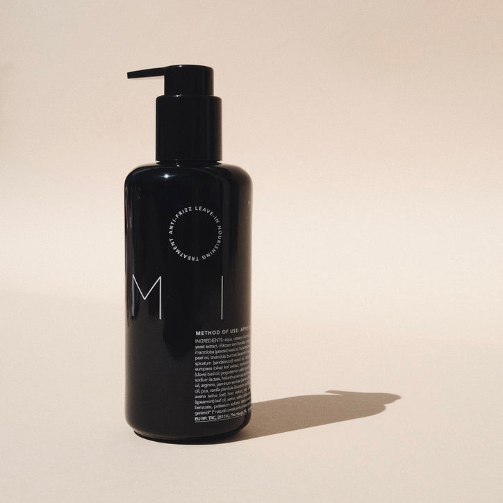 Milk XL is a black glass bottle with white text and a large black pump. It sits on a warm beige back drop.