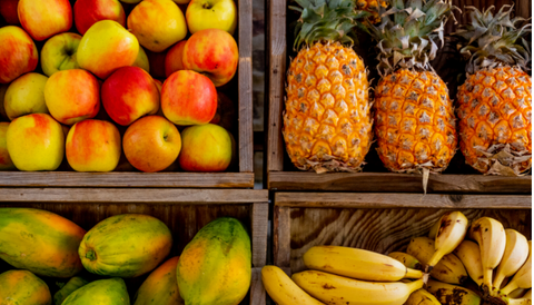 Four fruit boxes with pineapple, apple, mango and banana.