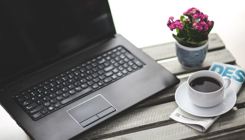 A wooden table with a computer, purple flowers, a magazine and a cup of coffee.