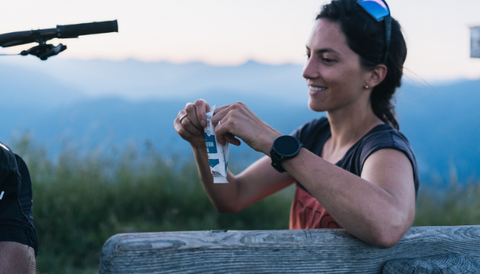 A girl with black hair is sitting on a wooden bench and is opening a Crownhealth protein bar after a mountain bike ride.