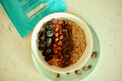 healthy vegan breakfast with 3-4 tbsp Oat flakes Vegetable milk Blueberries 20 g Hazelnuts (unroasted) Dark Chocolate (85-90%) recovery protein powder restore