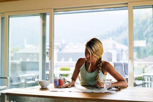 blonde girl looking at a map during breakfast with anti-inflammatory supplements on table
