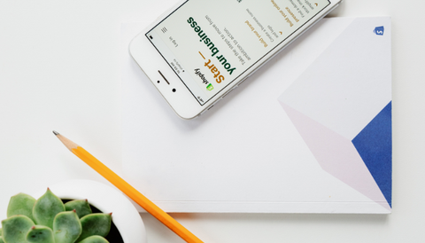 A white iphone on a white table with a pencil, a succulent and a paper folder. On the iphone you see the Shopify page.