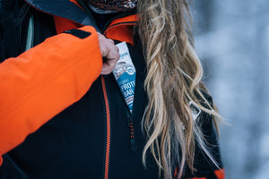 long blond curly hair woman grabbing an organic vegan protein bar with cocoa and almond butter, from her orange and black ski jacket front pocket while snow shoeing on fresh powdered snow in the swiss alps, in a cloudy day