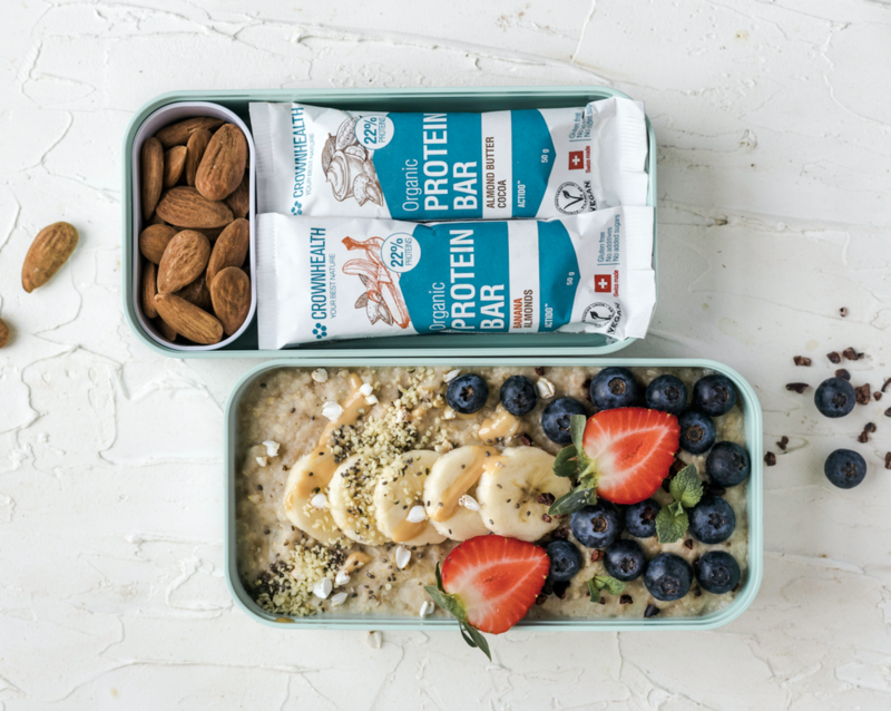 Healthy lunch bag with porridge, banana and berries, vegan organic protein bars by Crownhealth and almonds