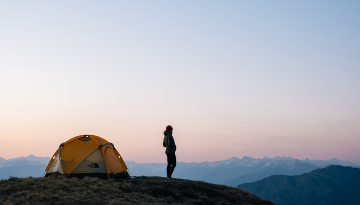 A girl in the mountains, in the Swiss Alps, enjoys the view near a camping tent.