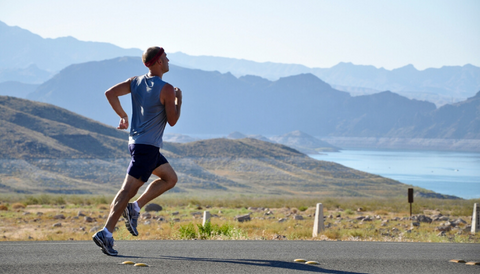 Man running in the street in front of mountains and a lake