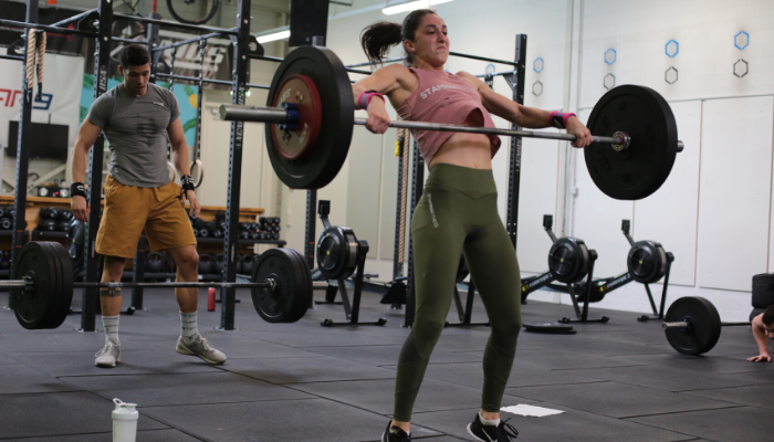 Two guys are working out at a Crossfit gym. The girl is lifting weights, while the man is resting.