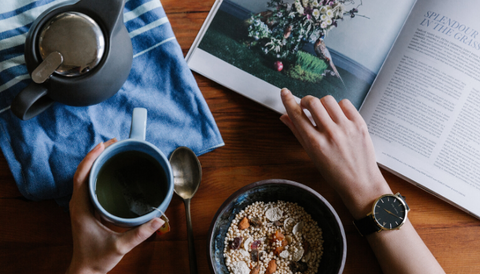 someone is having breakfast, reading the newspaper, drinking a cup of tea and eating a bowl of muesli. On the person's wrist there is a watch with a black dial