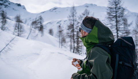 A yong and sporty boy eats his Crownhealth Energy Bar in the middle of the snowy mountains