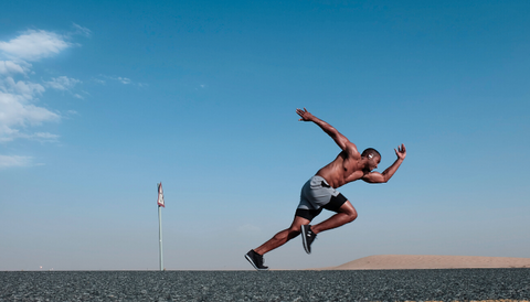 black man who is training in the street, in the open air, seems to be taking a run for jumping