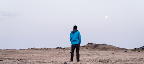 Man in a blue jacket stands alone in the middle of a valley of rocks.