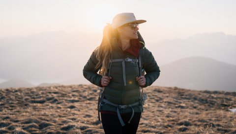 A girl in a white hat, green jacket and black pants looks at the mountain panaorama.