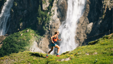 A blonde girl in an orange vest and blue pants is running in the mountains. In the background, there's a waterfall.