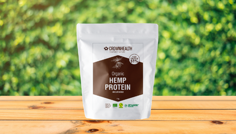 Crownhealth vegan protein powders on a wooden table. In the background you can see a garden with green grass and leaves.