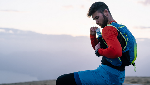 A boy with tufty hair, a blue vest, an orange shirt and blue shorts, is sitting on a bench in the mountains and is taking a Crownhealth protein bar.