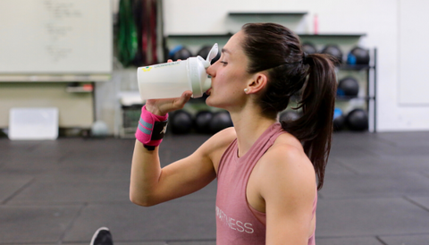 Girl Drinking Crownhealth Restore Powder at a Crossfit Gym
