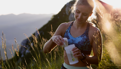 A girl pours Crownhealth's Restore Powder in the mountain shaker