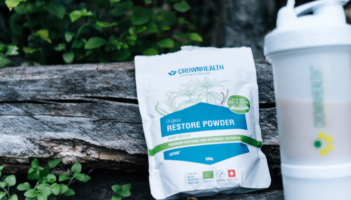 Crownhealth Restore Powder on a wooden bench next to the shaker