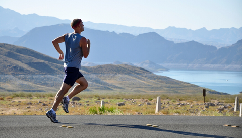 A blond guy, wearing a blue T-shirt and blue shorts, runs down the street. In the background, a lake and mountains.