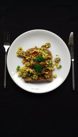 Organic Tofu scrambled on toast with mushrooms, lemon juice, Dijon Mustard, Garlic Powder, Frozen Peas Thawed, Onion, and Turmeric