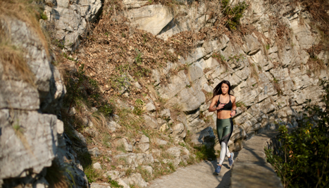 very beautiful young girl runs with a black bra and green pants on a path in the mountains