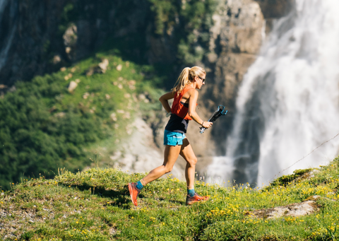 blonde and young girl in sports outfit runs in nature in front of a waterfall
