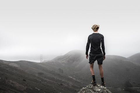 endurance sport runner looking at the cloudy ski from a mountain peak