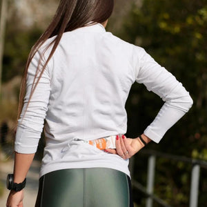 running girl taking an energy bar crownhealth from sports jacket pocket
