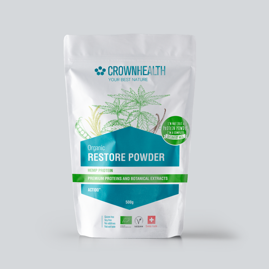 "Premium proteins and botanical extracts support muscle repair and growth. Crownhealth Restore Powder Hemp in a white standing 500g pouch , with colurful ingredients draws. Blue Crownhealth logo and designs. A light green circle saying: ""I'm not just a protein powder,I'm a complete recovery mix!"". Quality logos like organic certified, vegan, gluten free, soy free , no additives and swiss made  Edit alt text"