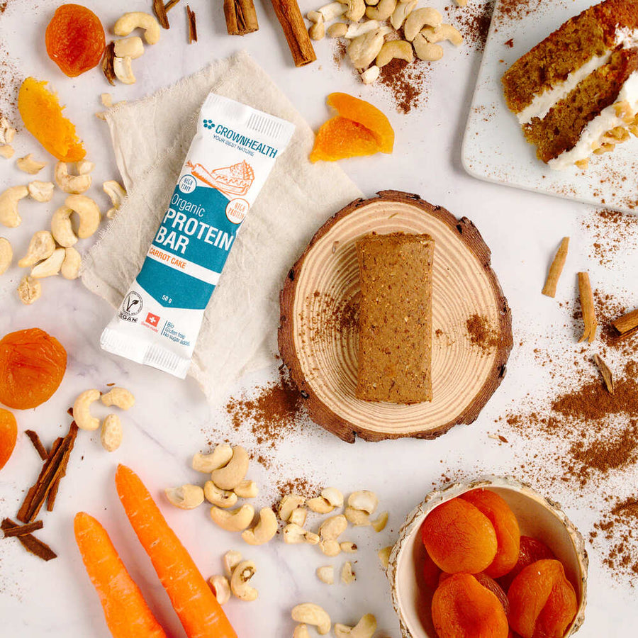 crownhealth carrot cake high protein bar rich in fiber on a white plate together with ingredients: dates, cashews, shredded carrot and cinnamon. All organic, plant based and natural healthy high protein snack for everybody and for everyday. on the background, carrots and a kaki napkin