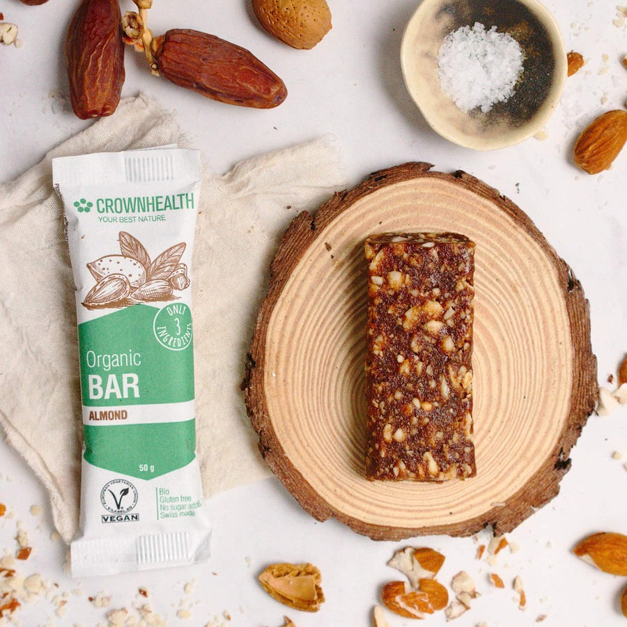 crownhealth salted almons bar on a white table  together with simple 3 ingredients: dates, almonds and salt. All organic, vegan and natural anytime healthy snack