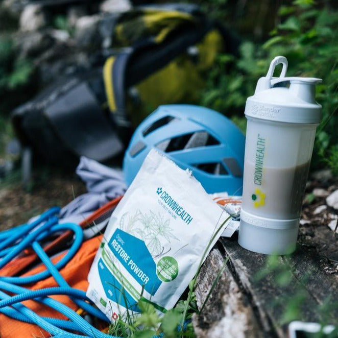 "Climbing gear and recovery shaker ready after training. Premium proteins and botanical extracts support muscle repair and growth. Crownhealth Restore Powder Hemp in a white standing 500g pouch , with colurful ingredients draws. Blue Crownhealth logo and designs. A light green circle saying: ""I'm not just a protein powder,I'm a complete recovery mix!"". Quality logos like organic certified, vegan, gluten free, soy free , no additives and swiss made."