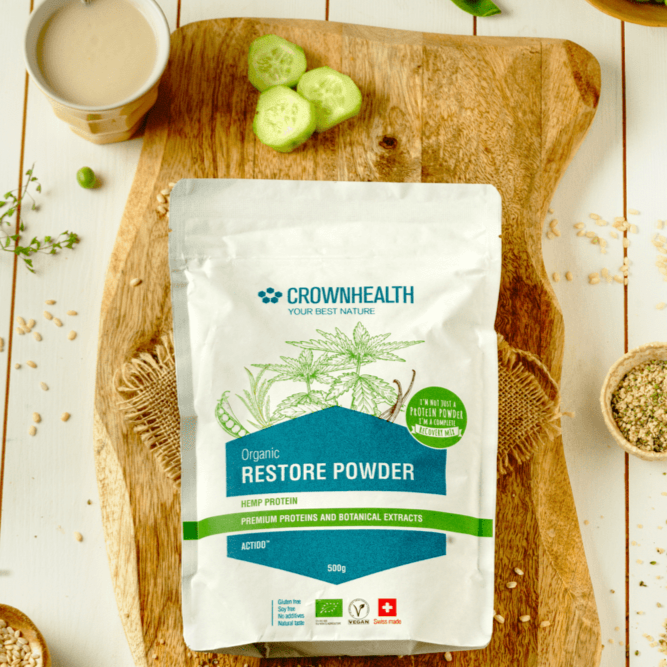 "Restore Powder Spirulina 500g eco-friendly pack. Premium proteins and botanical extracts support muscle repair and growth. Crownhealth Restore Powder Hemp in a white standing 500g pouch , with colurful ingredients draws. Blue Crownhealth logo and designs. A light green circle saying: ""I'm not just a protein powder,I'm a complete recovery mix!"". Quality logos like organic certified, vegan, gluten free, soy free , no additives and swiss made"