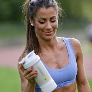 girl shaking a sports shaker after running workout. Crownhealth multi-functional eco-friendly shaker with blenderball for sports nutrition