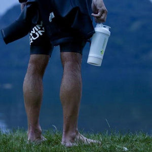 swimmer holding a sports shaker after workout. Crownhealth multi-functional eco-friendly shaker with blenderball for sports nutrition